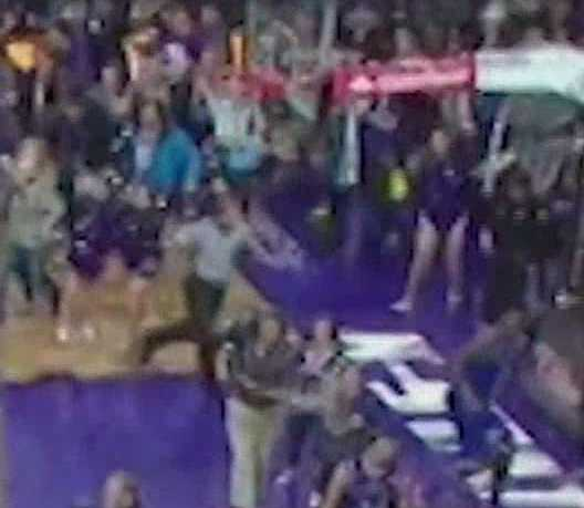 A KU player is run into by a fan and makes for the baseline.