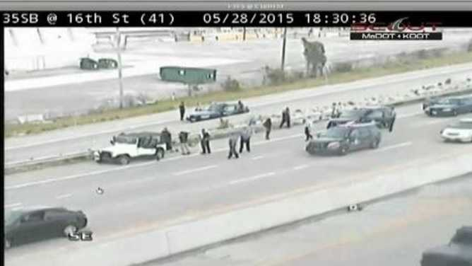 Kansas City police throw stop sticks under a jeep to end a chase at the north end of the Bond Bridge.