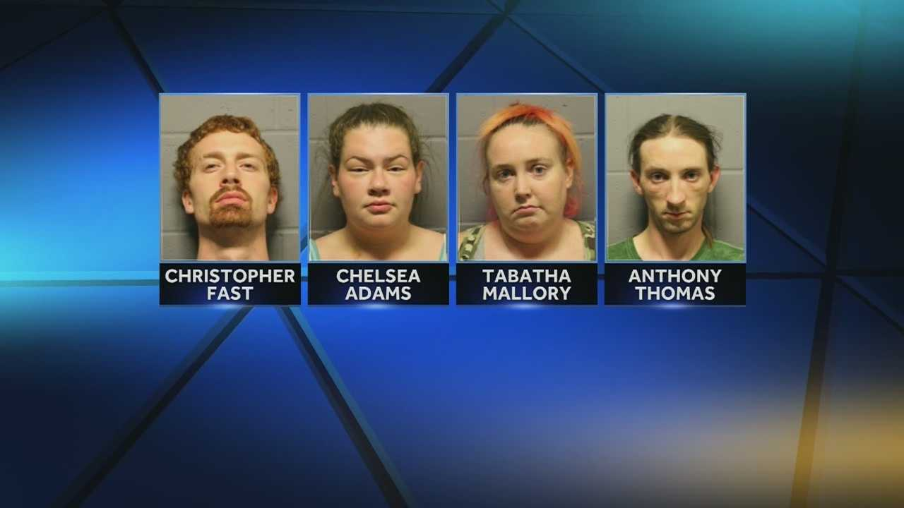 Four people have been charged after a woman told police that she was restrained and beaten over several days at a southeast Lawrence home.
