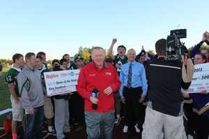 NFL Hall of Fame quarterback Len Dawson helps deliver two $500 checks to each school from HyVee as part of the game of the week festivities.