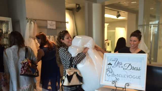 Marita Perez takes home her bridal gown. She's planning a July wedding. The gowns are available for free at Belle Vogue for brides who either are in the military or their spouse to be is in the military.