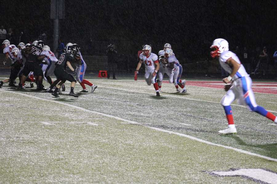 Quarterback Matt Wright scrambles in a rainy fourth quarter, injuring his knee on the play.