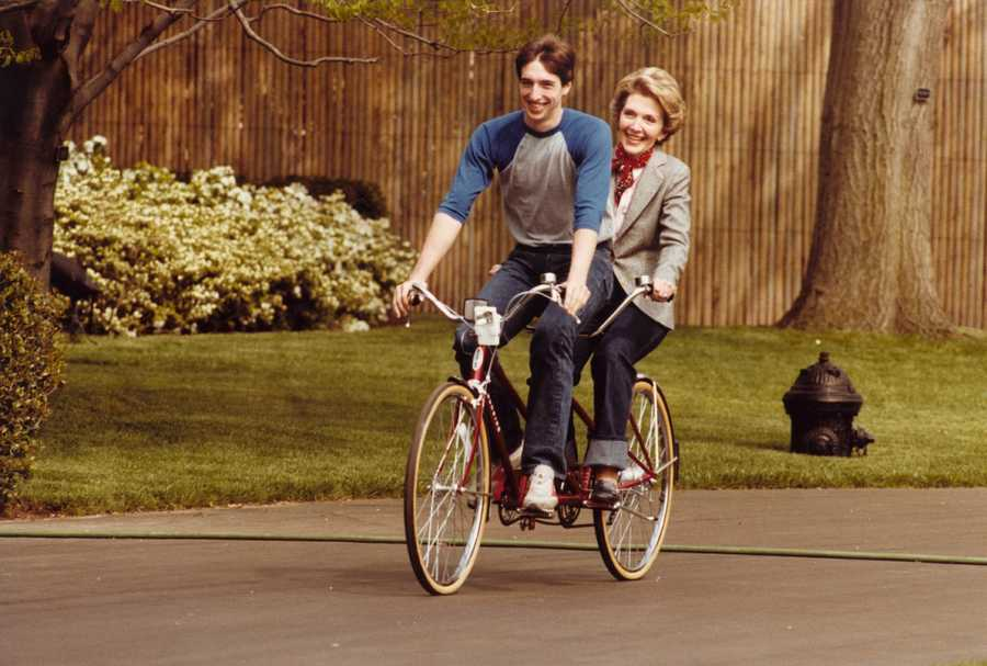 First Lady Nancy Reagan rides an tandem bicycle with son Ron Reagan on the south grounds of the White House. (April 22, 1981)