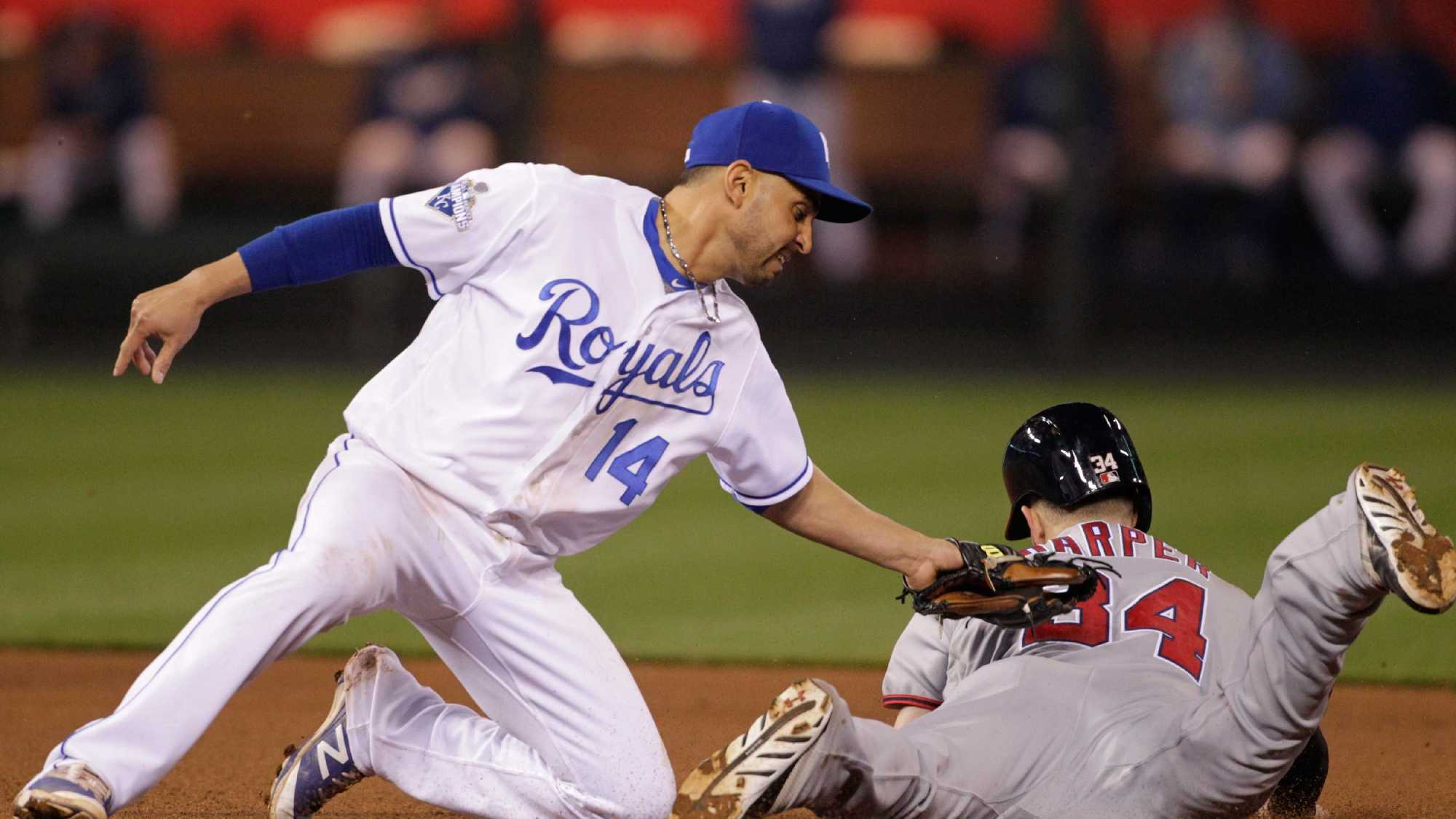 Kansas City Royals second baseman Omar Infante (14) tags out Washington Nationals Bryce Harper (34) as he attempts to steal second base in the sixth inning of a baseball game at Kauffman Stadium in Kansas City, Mo., Monday, May 2, 2016. (AP Photo/Colin E. Braley)