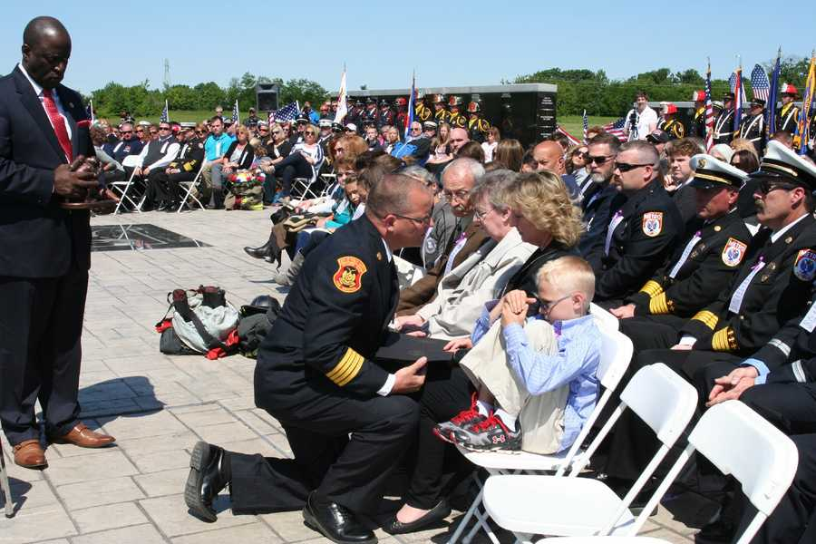 The family of fallen firefighter Christopher Tindall is presented with a proclamation from Gov. Jay Nixon and a fallen firefighter statue.