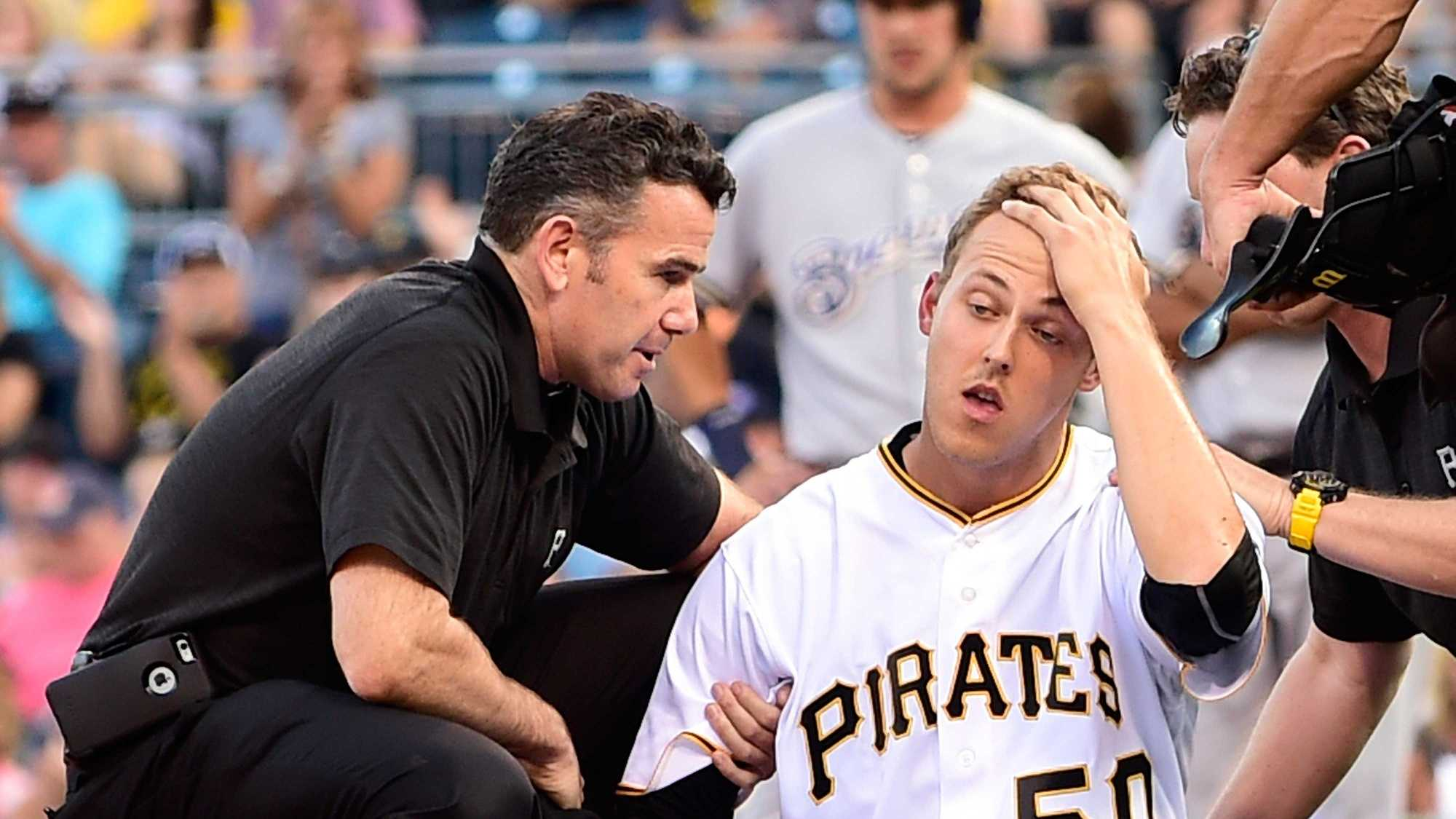 Athletic trainer Ben Potenziano, left, watches Pittsburgh Pirates starting pitcher Jameson Taillon (50) hold his head in the second inning of a baseball game against the Milwaukee Brewers in Pittsburgh, Tuesday, July 19, 2016. Taillon was hit by a ball off the bat of Herman Perez, but stayed in the game. (AP Photo/Fred Vuich)