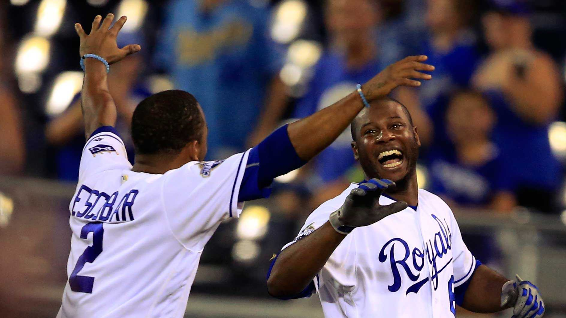Kansas City Royals' Lorenzo Cain, right, celebrates with Alcides Escobar after driving in the winning run in a baseball game against the Chicago White Sox at Kauffman Stadium in Kansas City, Mo., Wednesday, Aug. 10, 2016. The Royals defeated the White Sox 3-2 in 14 innings. (AP Photo/Orlin Wagner)