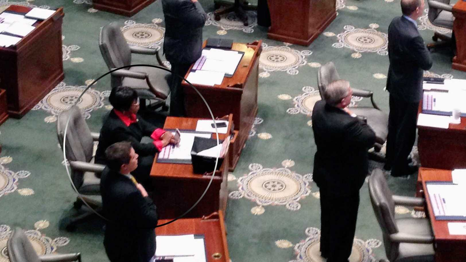 Missouri state Sen. Jamilah Nasheed, a St. Louis Democrat, sits, third from left, while her colleagues recite the Pledge of Allegiance in the state Capitol in Jefferson City on Wednesday, Sept. 14, 2016. Nasheed says her silent protest on the Senate floor was intended to show solidarity with San Francisco 49ers quarterback Colin Kaepernick, who has kneeled for the national anthem in protest of police brutality and racial oppression. (AP Photo/Summer Ballentine)