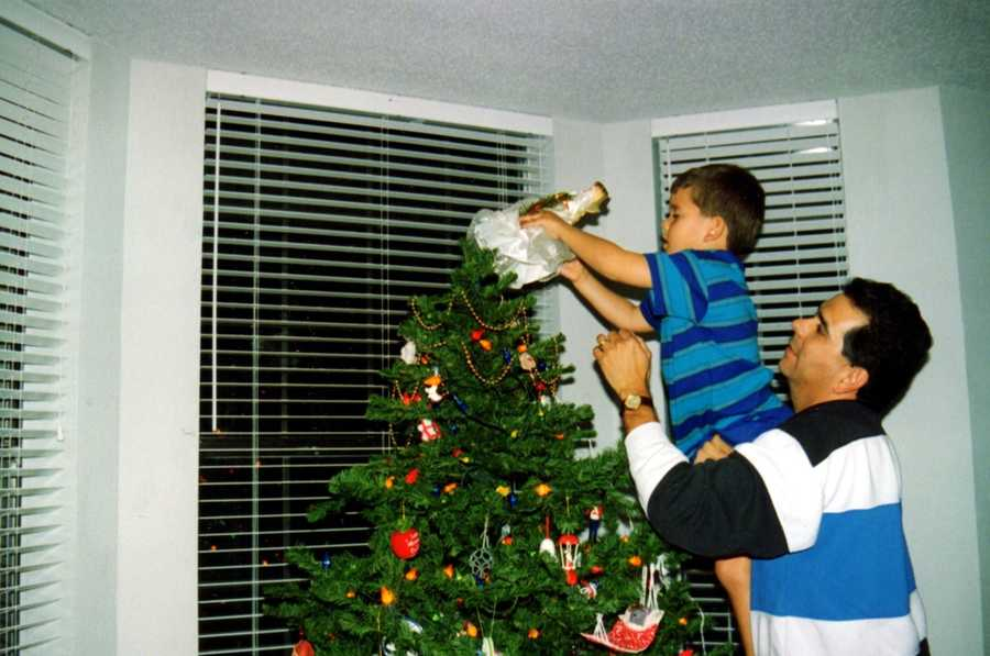 """Joe said, """"The big event after the tree was decorated was when I would lift one of the boys to place the angel at the top, here is our youngest David performing that task."""""""