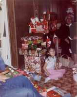 """This picture was taken in 1981.  I was 6. It depicts one of my greatest childhood memories of Christmas.  My beautiful grandmother is sitting behind me.  Our family tradition was to gather at her house in Los Alamos for Christmas Eve.  We would snack on my grandmother's Italian cookies, eat a great meal of pasole and tamales, then pass out gifts and spend hours going in a circle, opening our gifts one at a time.  Everyone got to appreciate and enjoy what each person received.     For the past few years, I have hosted Christmas Eve dinner at my house.  An honor I am proud to hold as my grandma once did.  The menu has changed.  My children request brisket and homemade mac n' cheese, but the tradition of family and shared gift giving remains.  My children now sit with a pile of gifts next to their grandparents and enjoy the spirit of giving.  Merry Christmas New Mexico....and much love to you Grams as you watch over us from above,"" Marisa said."