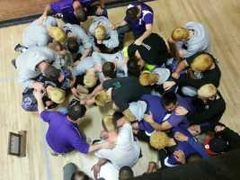 MHS wrestlers gather together and pray after a tournament.