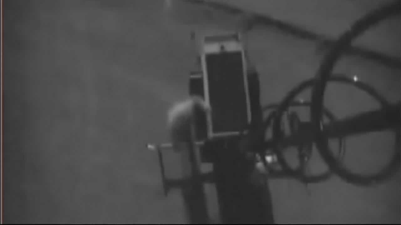 A pair of vandals trying to break APD's mobile video surveillance trailer.