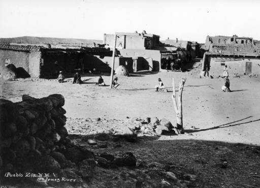 Pueblo Zia, N.M. on Jemez River in 1879: View north over south plaza of Zia Pueblo, New Mexico, shows Native Americans sitting on sacred rocks, a Christian cross, and adobe house blocks.