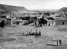 Pueblo San Felipe in 1879: View overlooking the Native American pueblo of San Felipe Pueblo, New Mexico, shows adobe buildings, Santa Ana mesa, adobe brick ovens, and people sitting.