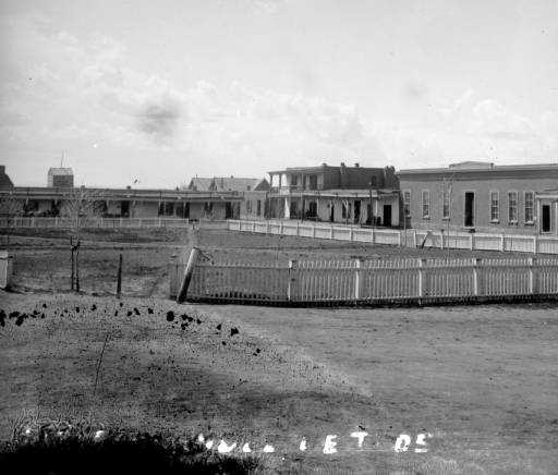 Rancho de Taos in 1875: Stereographic view of flat-roofed, adobe buildings along a plaza, either in Taos or the Ranchos de Taos in New Mexico&#x3B; scene includes: white picket fence, small trees with bare branches in the plaza, dirt paths, and a two-story building with a balcony facing the plaza.
