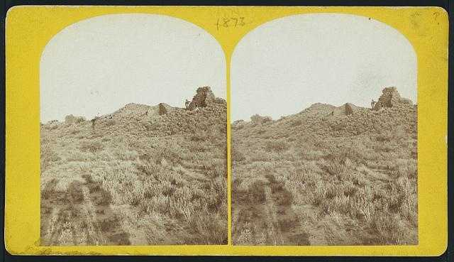 Ruins of Pueblo San Juan, N.M. in 1874: Photograph showing a man standing in the corner of a ruin.