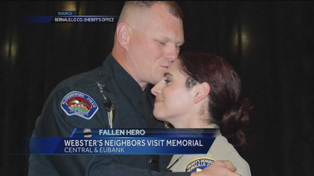 Slain Officer Daniel Websters neighbors visit his memorial site.