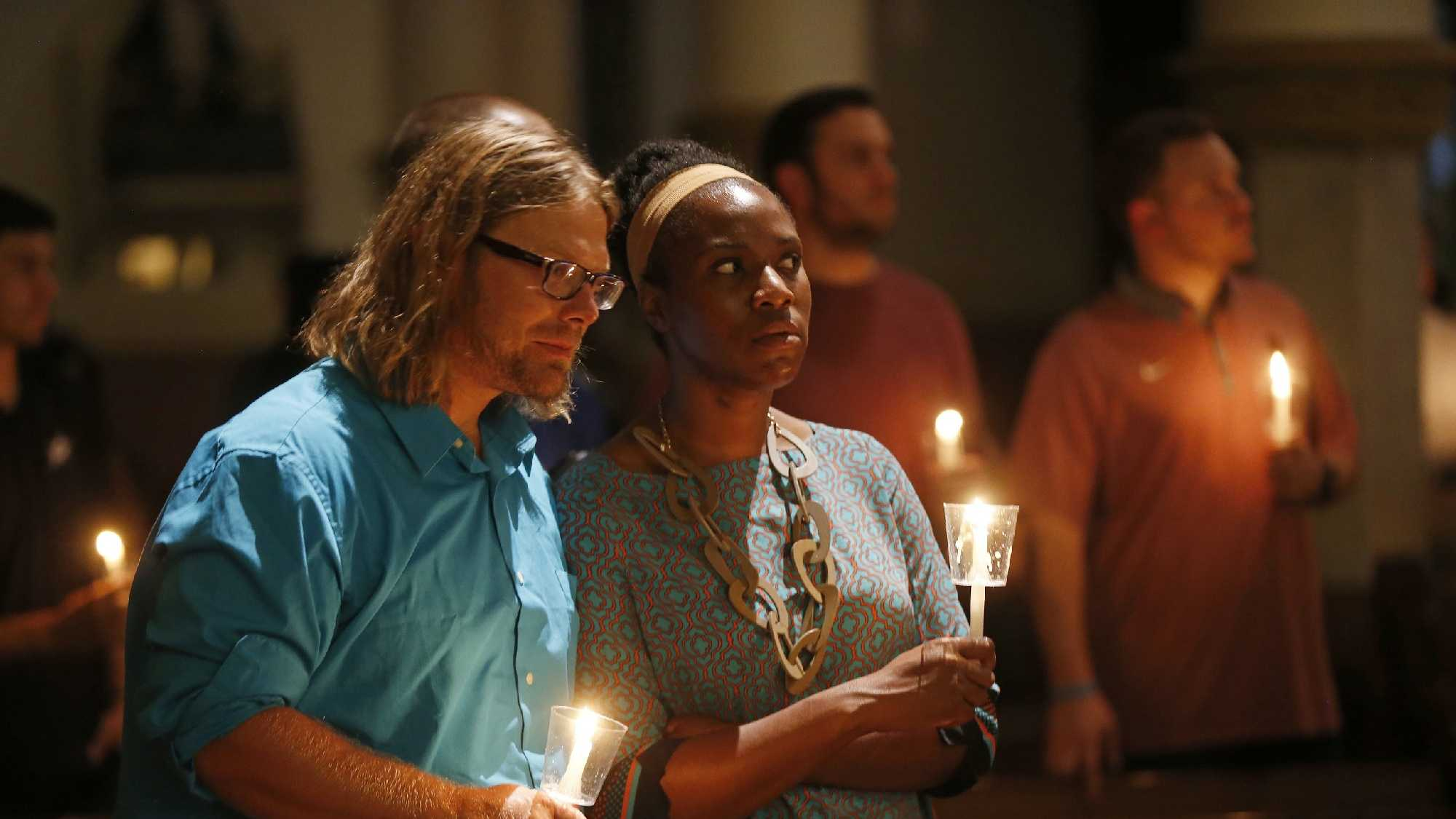 "Lily Reagan and Kenneth McCarroll pray during a ""United To Heal Prayer Vigil"" at Cathedral Guadalupe, in honor of the Dallas police officers who were slain Thursday."