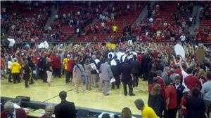 Fans celebrate the Mountain West title with the New Mexico Lobos on the court.