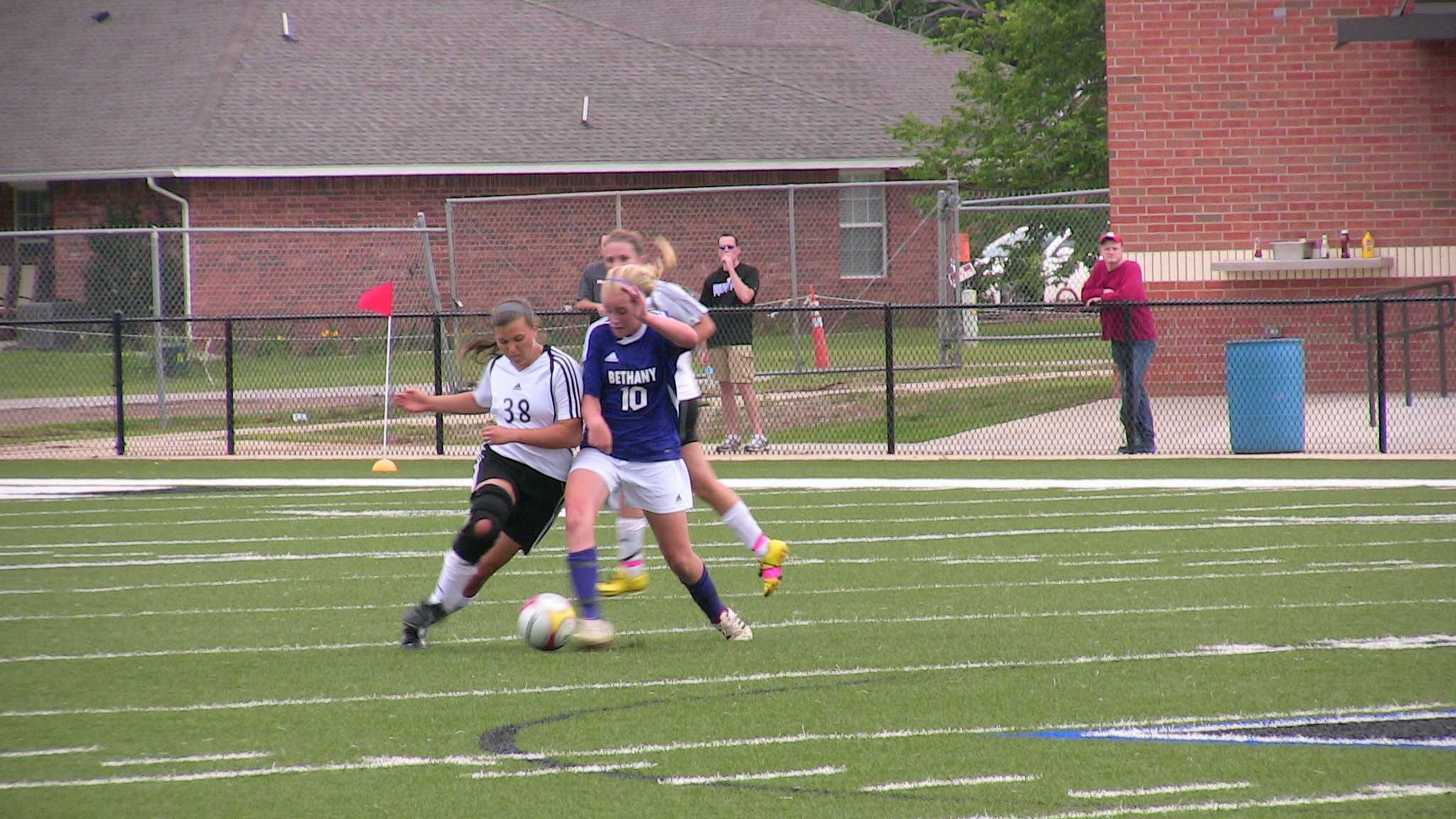 The Bethany Bronco's battle the Verdigris Cardinals in the 4A girls soccer championship. Here two players battle for the ball.