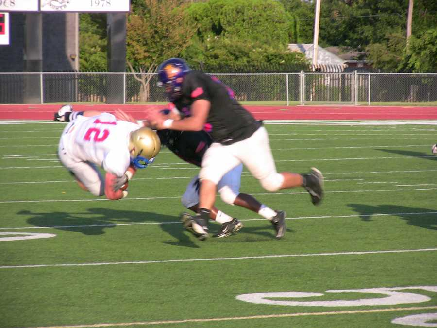 Urban defenders chase down and tackle suburban quarterback Jake Phillips who was pressured the entire game.