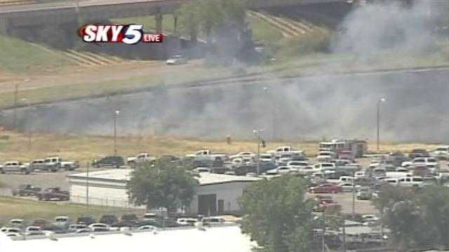 Firefighters battle a blaze near the Will Rogers World Airport on Monday midday. Sky5 is above the scene.