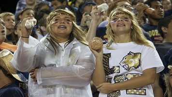 Shaking plastic bottles filled with rocks, these two Sabercat fans bare the rainy and cold weather.