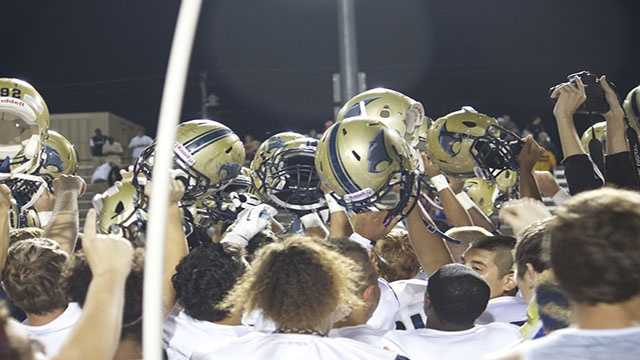 The Sabercats with helmets held high, break down a huddle after a tough 33-27 victory in double overtime.