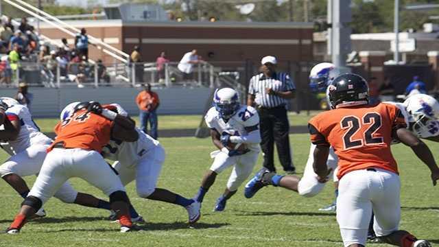 Millwood running back Janari Glover (21), carries the ball toward an opening.