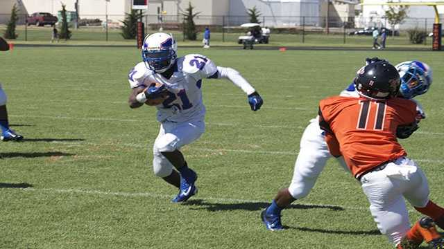 Janari Glover (21), rushes upfield on a run play for the Falcons.