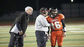 Quarterback Zach Long talks to head coach Greg Nation and coach/father Chuck Long, is nearby.