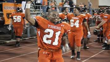 """Imond """"Bam Bam"""" Robinson (21) holds his helmet high and can't help but smile after giving Mustang their first loss of the season."""