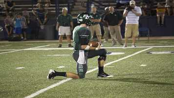 Santa Fe quartback, Justice Hansen (11), kneels to runout the clock and end the game.
