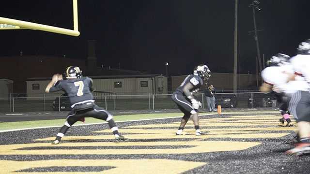 Midwest City back-up quarterback, Kilby McGuire (7), looks to throw downfield while being pinned in his own end zone.