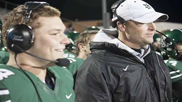 Senior Jaxon Uhles stands beside head coach Wade Standley on the sideline. He took a little time to bond with coach on the headsets. Maybe preparing for his post football profession?