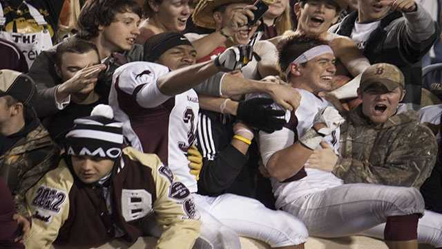 Seniors Stefan Davis (34, left) and Kyle Self (1, right side), climb into the student section to celebrate after winning the Class 3A state championship Friday night.