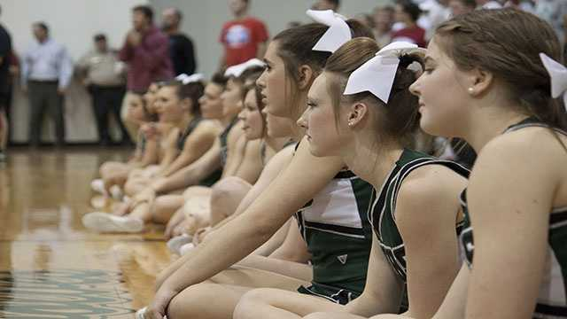 Norman North cheerleaders watch the dual while sitting near the mat.