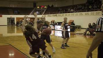 A Norman High player has a run-in with a Edmond Memorial player Jessica Foster (14).