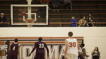 Cooper Clark (12) shoots a three-point shot Friday night to try and keep the Tigers in the game against the Edmond Memorial Bulldogs.