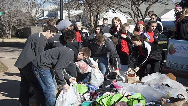 Students from Bishop Kelley take a turn to grab and load donations.