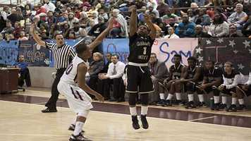 Mikey Smith (1), takes a three-point shot while defender Jordan Woodard (10) stays as close as possible.