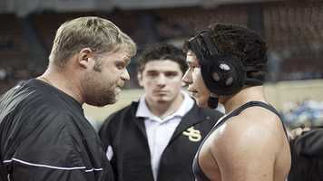 Sand Springs wrestler Nick Bearshead talks with his coach during the Class 6A consolation finals.