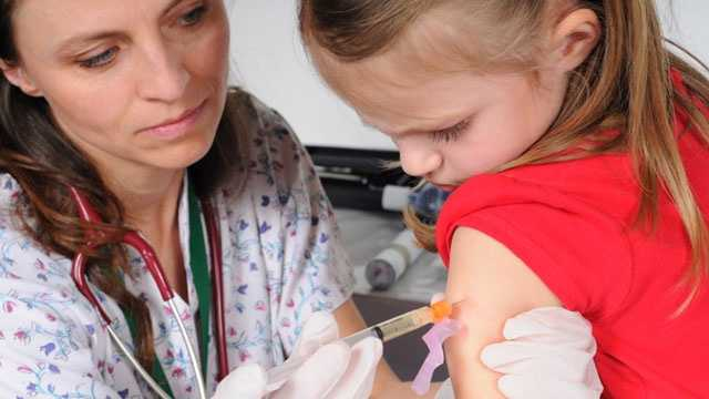 Girl getting vaccination from doctor