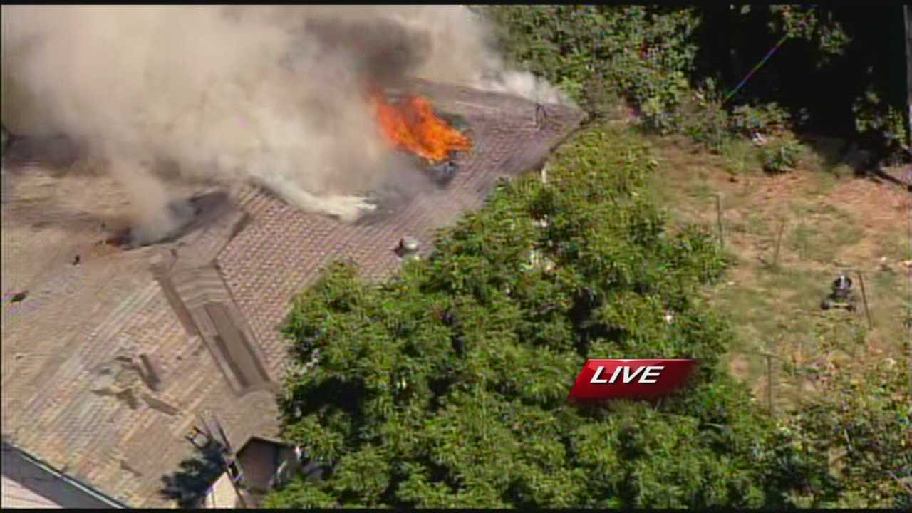 OKC firefighters battle a blaze as smoke emerges from an OKC home Monday