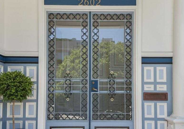 Period details are evident inside and out, top to bottom. Wrought-iron quatrefoil rims the glass entry doors.