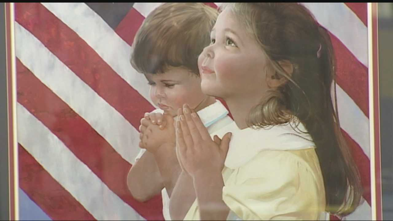A national group wants a Putnam City middle school to remove a photo of two children praying in front of a flag.