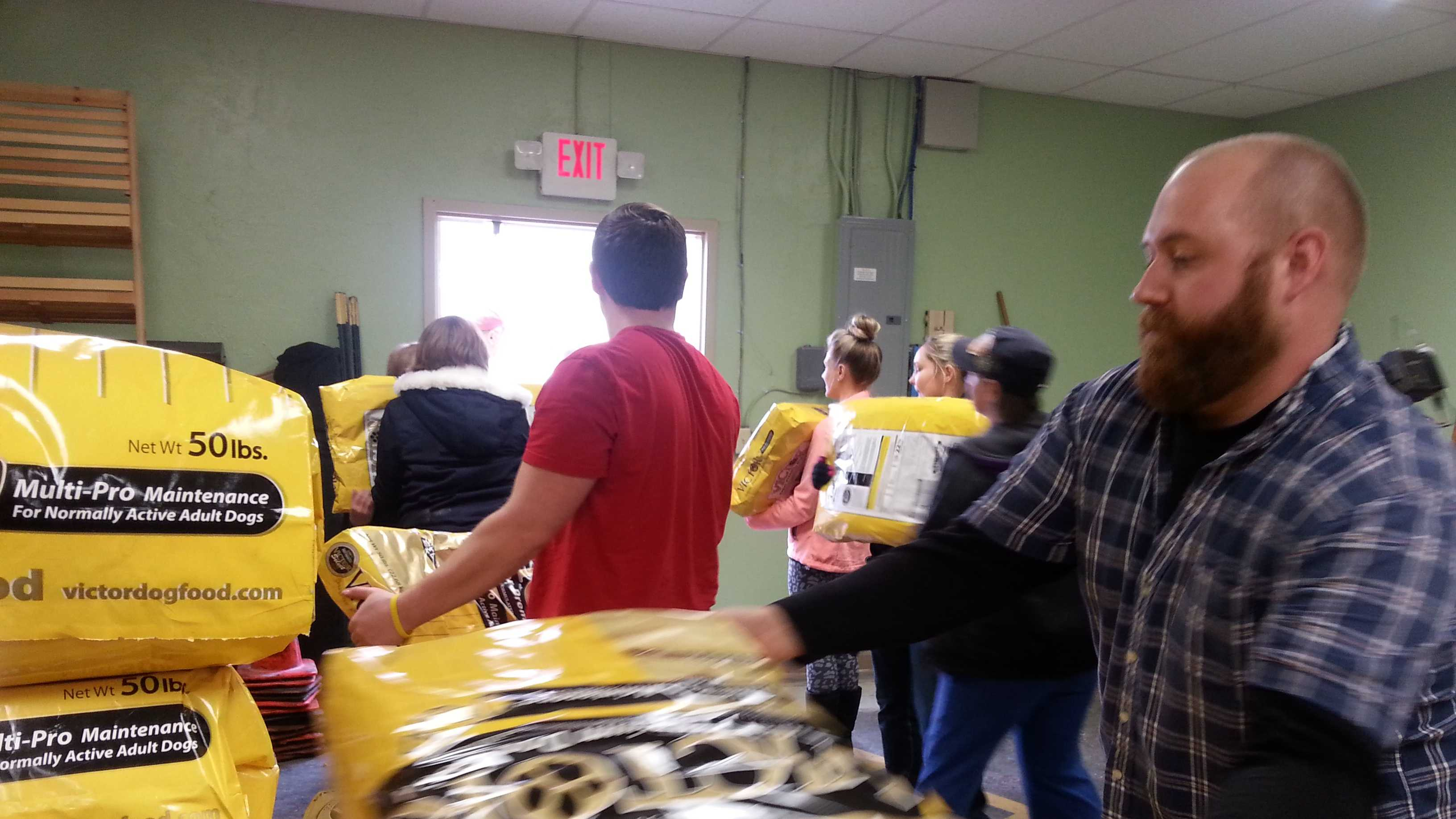 A long line of volunteers packed nearly 10,000 pounds of dog food onto trailers Saturday.