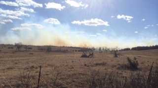 Firefighters were battling a large grass fire Sunday in Lincoln County, officials said. Crews contained the fire, which was north of Wellston, according to Lincoln County Emergency Management.