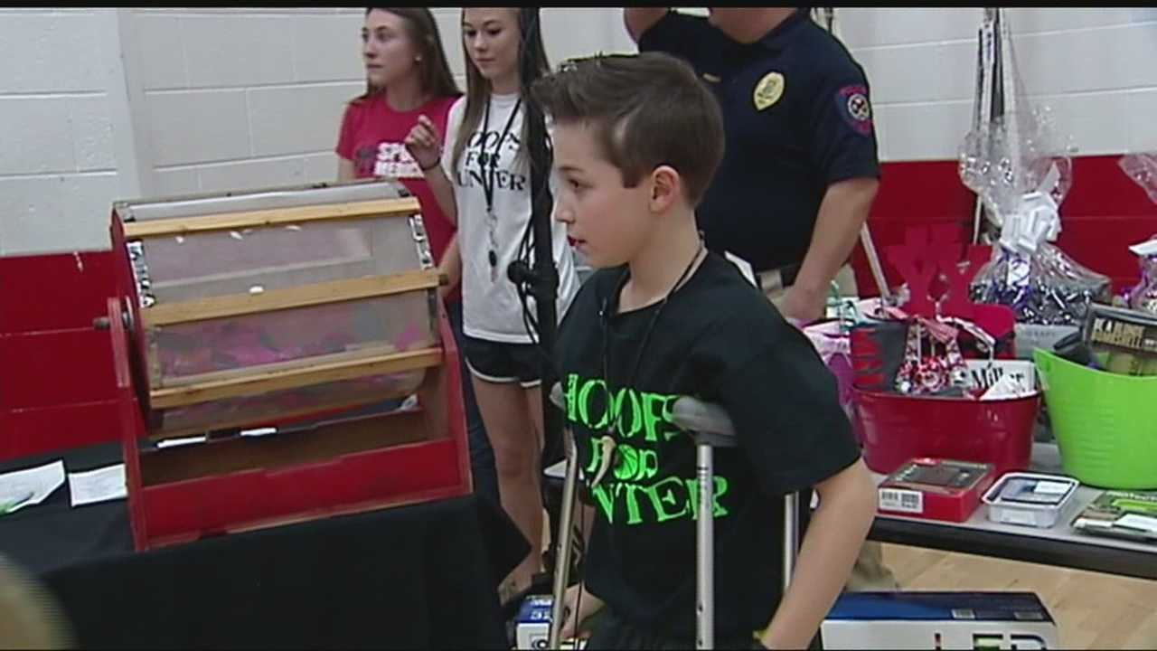 Yukon police and firemen took the basketball court to raise money for the boy.