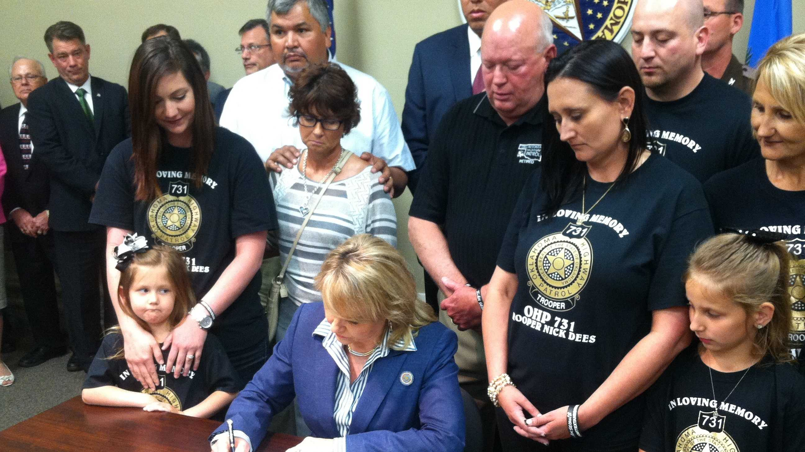 Governor Mary Fallin, joined by family members of Trooper Nicholas Dees and Trooper Keith Burch, signs HB1965.